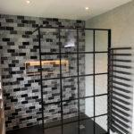 Black grid shower panel. Metro brick wall tiles and black shower inline tray