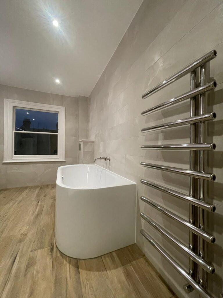 Steel bath, industrial taps and radiator on wall