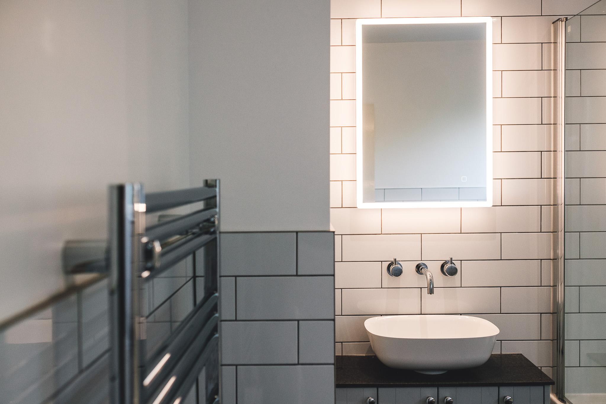 Sit on basin bowel with LED mirror above. Metro tiles on bathroom walls