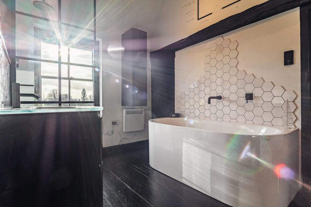 Steel bath, with hexagonal tiles, black fitted furniture and brassware walk in shower and tall boy next to itor