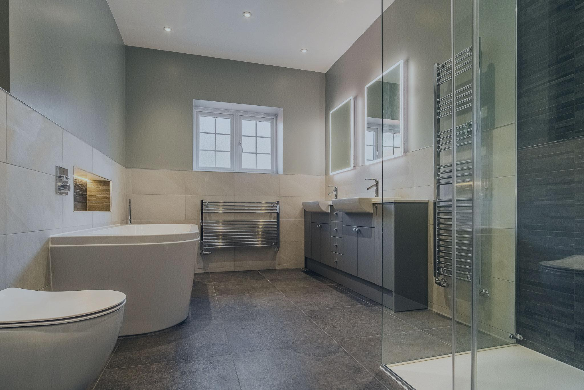 Fitted furniture in grey, with two LED mirrors above, radiators either side of the furniture. Shower enclosure, acrylic bath, toilet and two towel rails