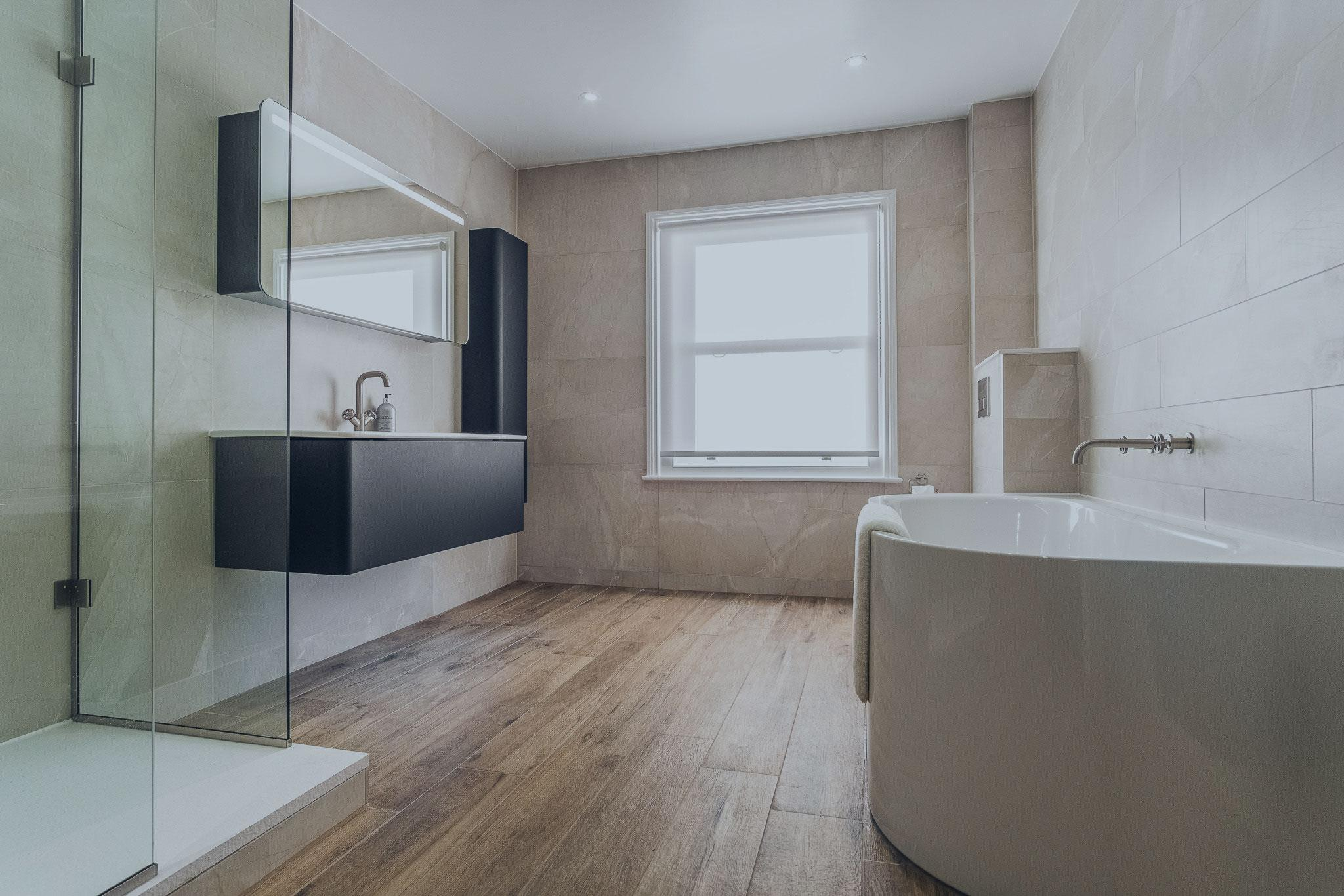 Steel bath, black fitted furniture with LED mirrored cabinet, industrial taps, walk in shower and wood effect bathroom floor