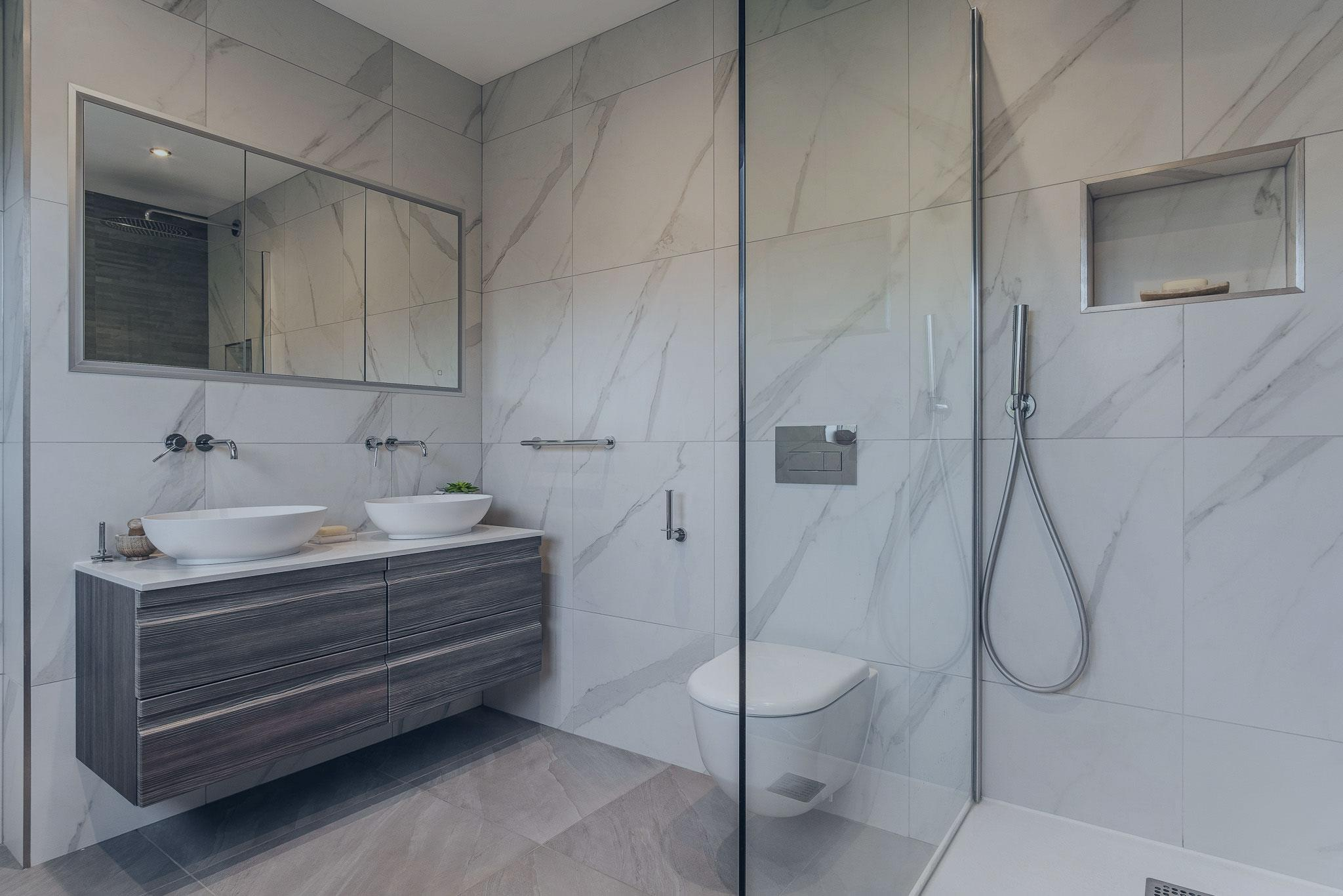 oak effect floating vanity unit with sit on basin bowls above recessed LED mirror. Walk in shower and toilet. Carrera marble tiles are in on the bathroom walls