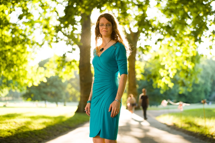 AWAD CEO Susan J Mumford stands in blue dress in Green Park, with sunshine and trees in background