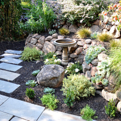 Arch cut stones with black mulch and moss rock boulder