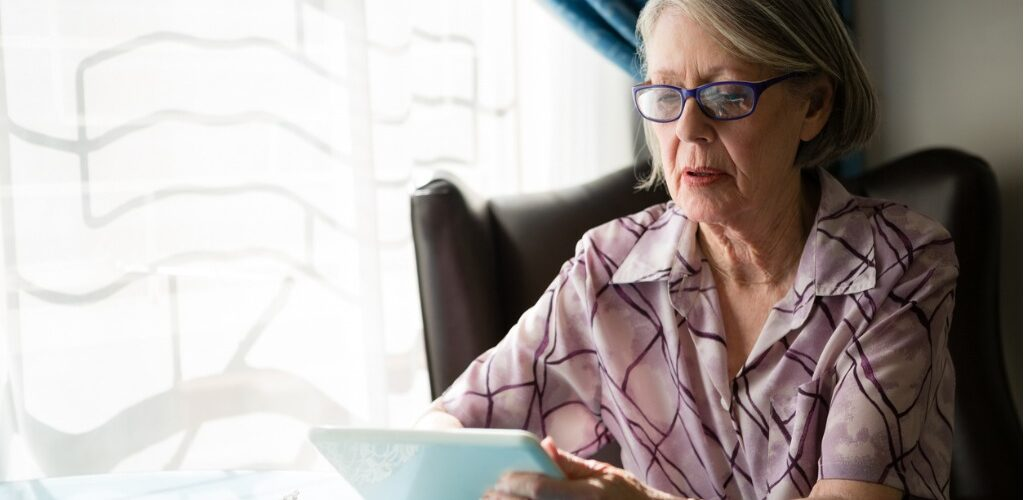 Care home resident using computer tablet.