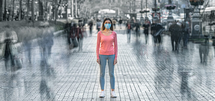 Woman with medical mask in crowded street