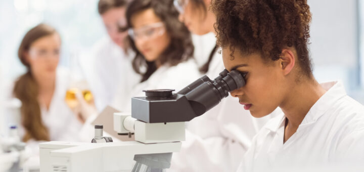 Science student looking through microscope in a laboratory