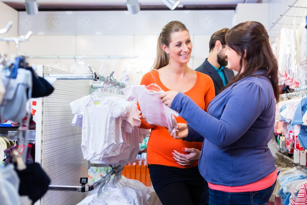 Salesperson with couple buying baby clothes in shop