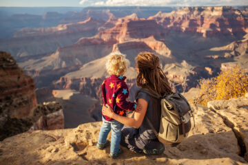 Mother and child standing on edge of Grand Canyon