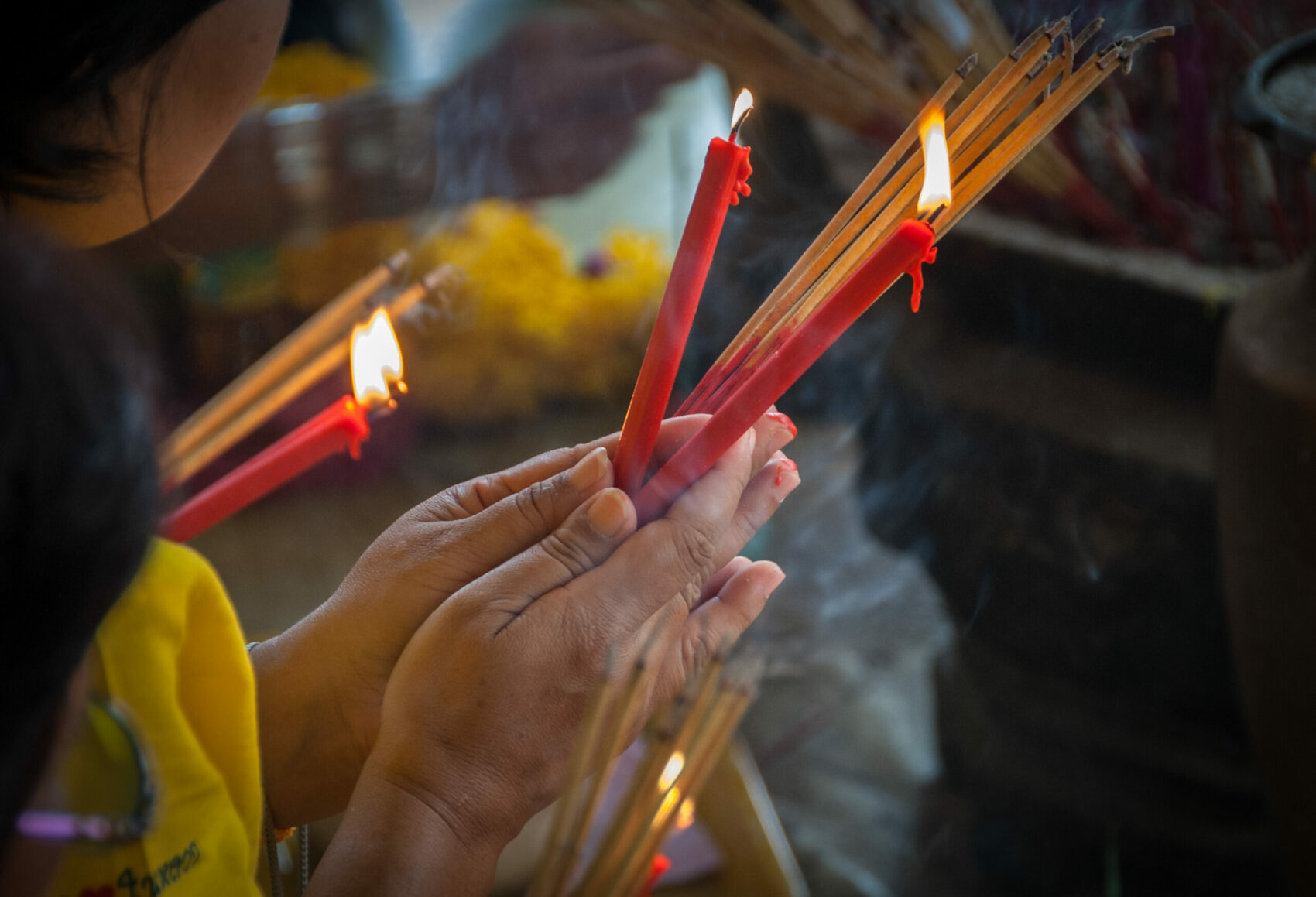 Woman's hands in prayer at Buddhist shrine in Bangkok