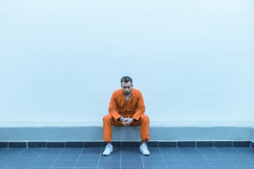 Prisoner sitting on bench in prison room