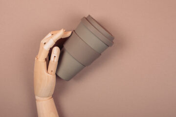 Wooden hand holding reusable cup of coffee