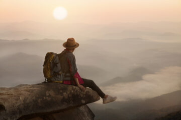 Backpacker man sitting on cliff with sunset background