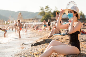 A woman in a swimsuit and a straw hat is sunbathing on the beach wearing medical mask on her face
