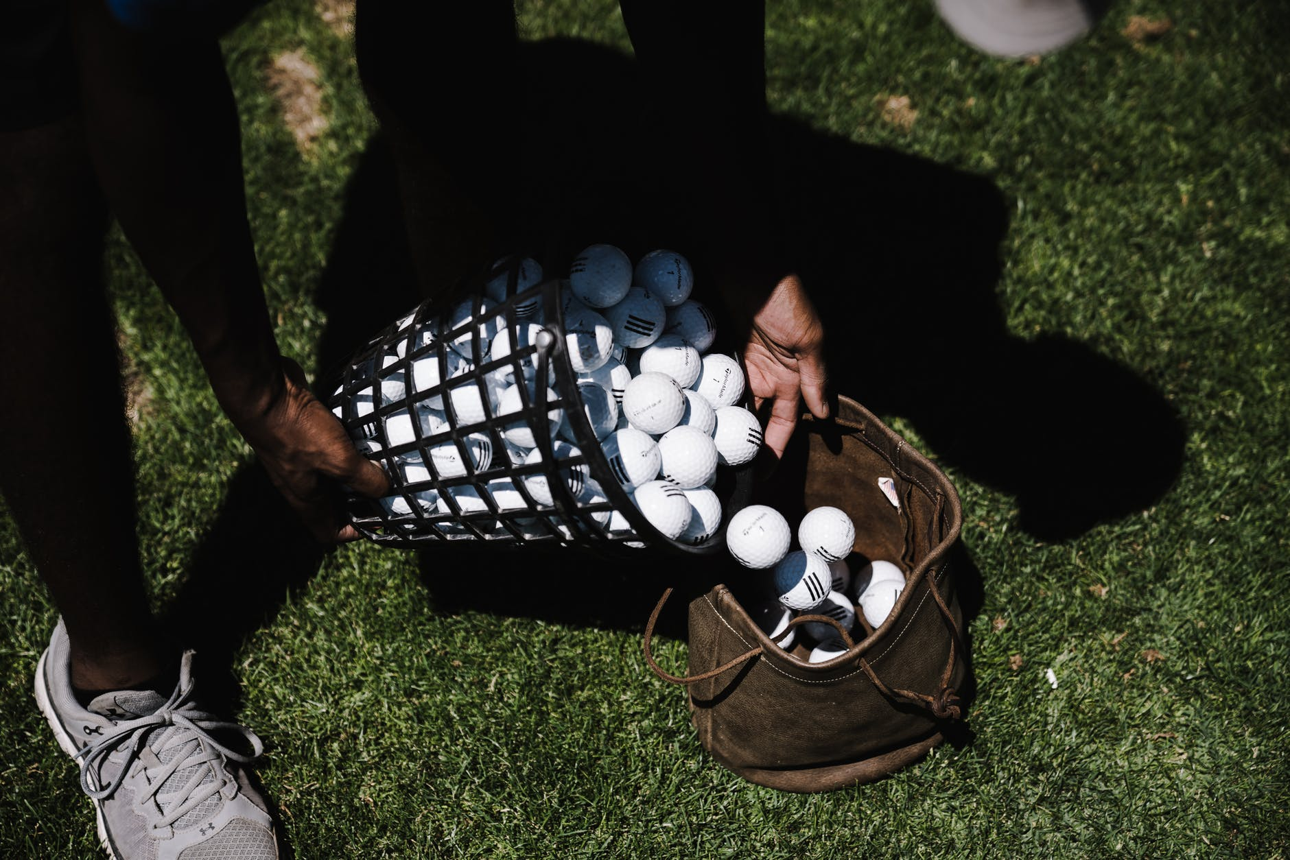 person pouring golf balls in brown leather bag