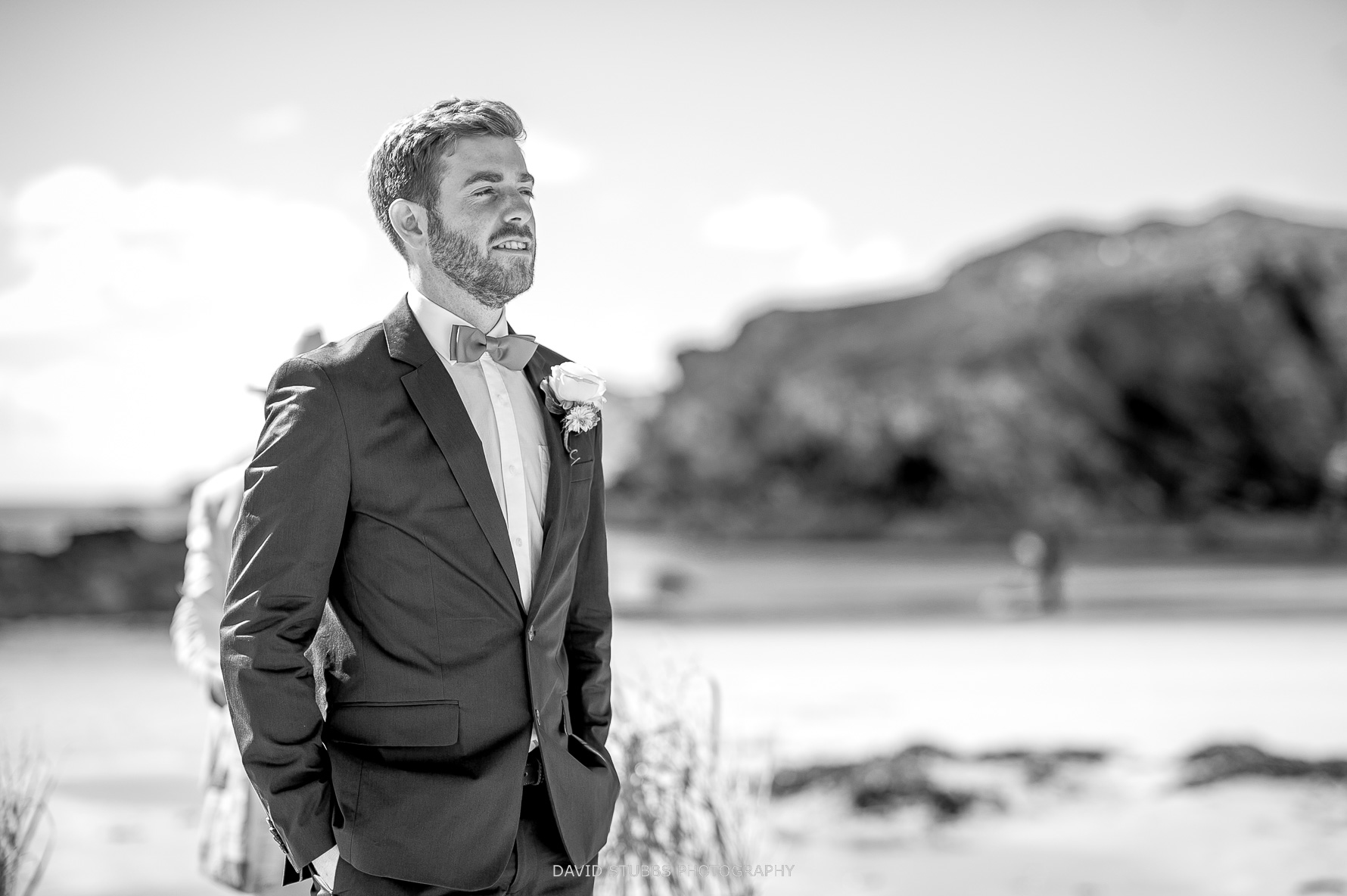 groom watches his bride walk across the sand
