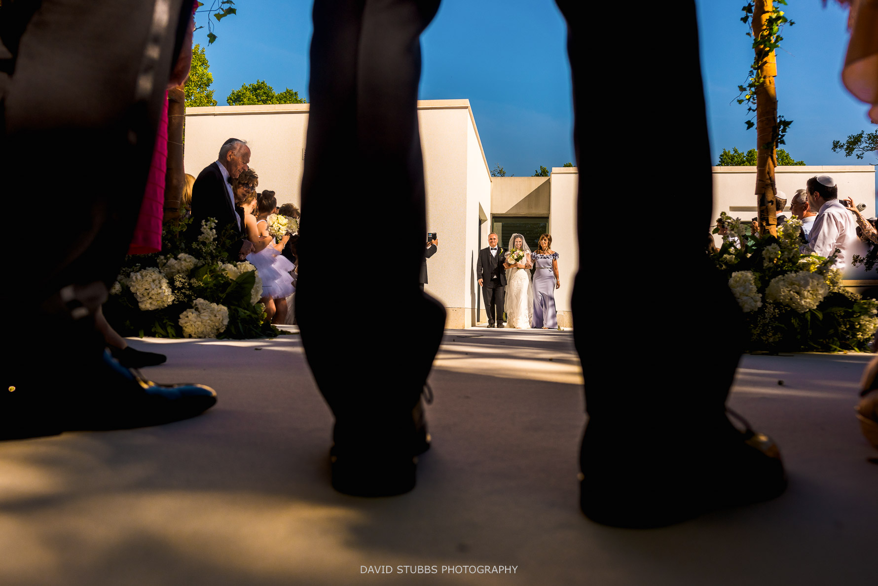 bride arriving photographed through the grooms legs