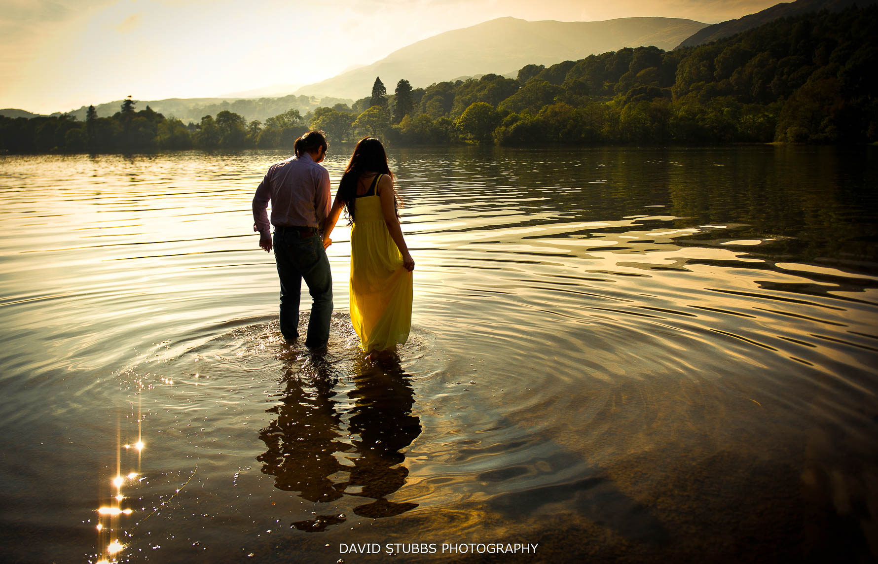 newlyweds walking out into coniston water