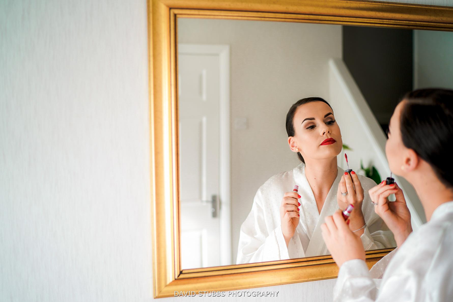 bride applying red lipstick