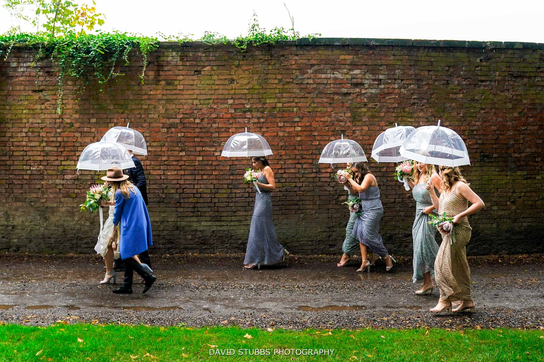 bridesmaids all walking under umbrellas