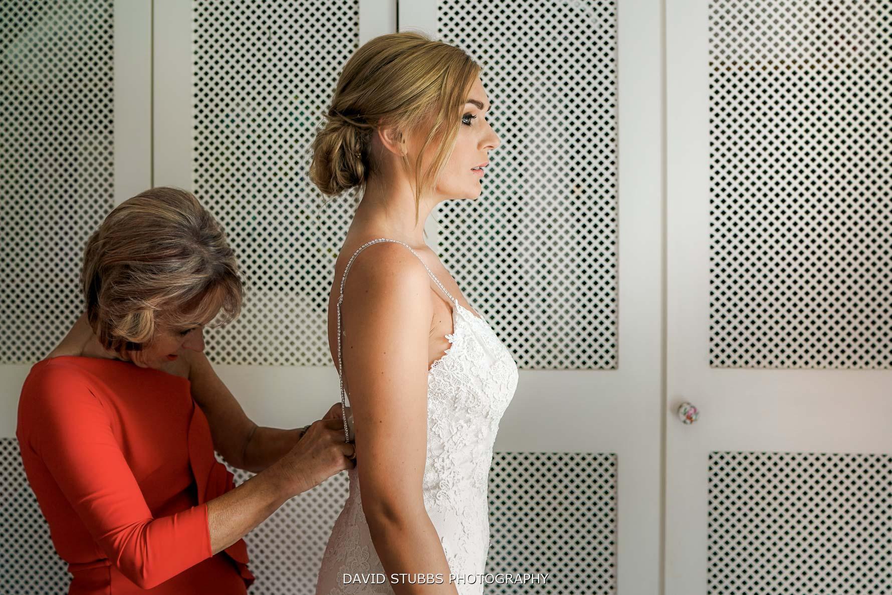 side on composition of bride having her wedding dress put on