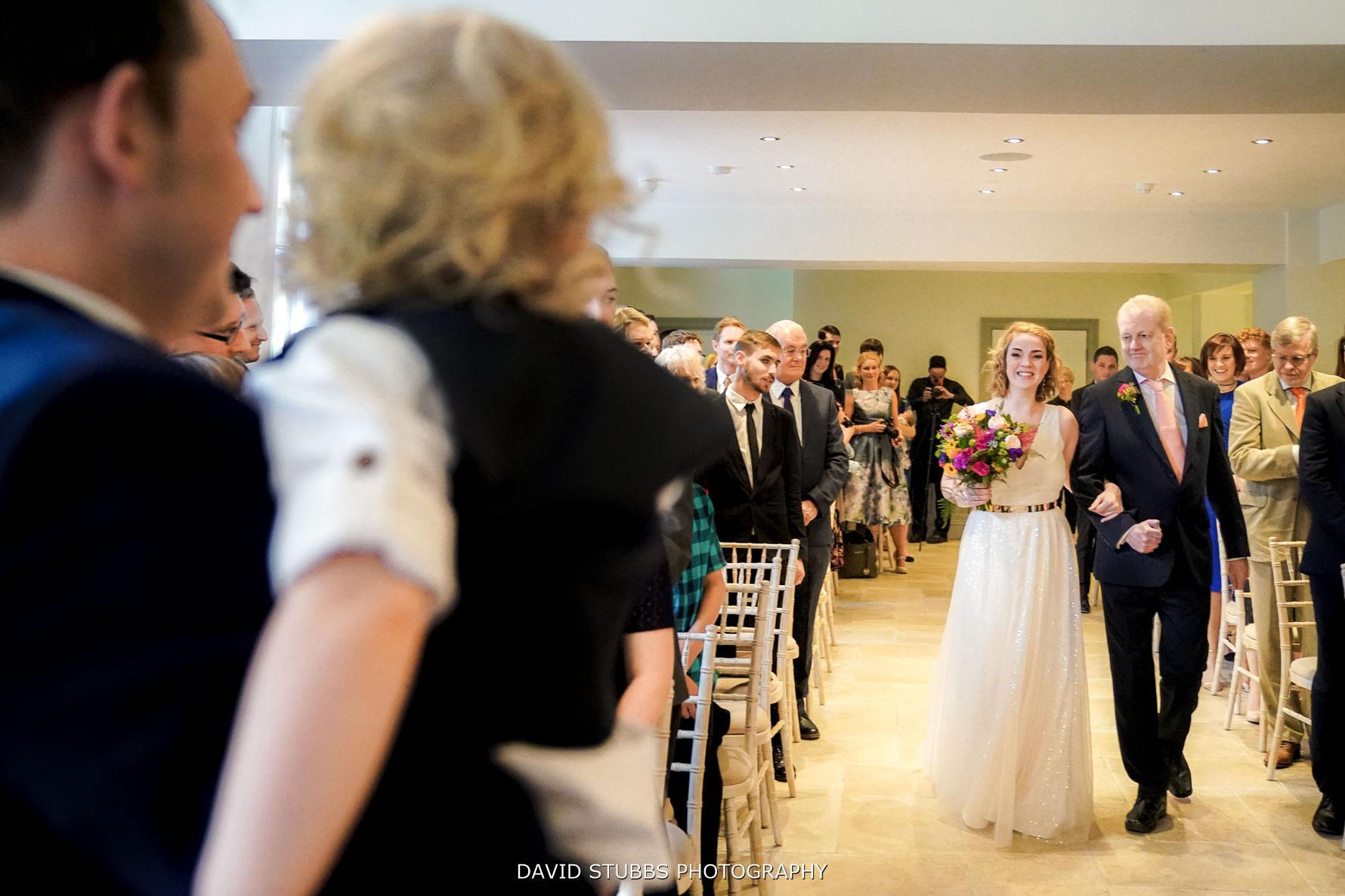 walking down the isle for their wedding ceremony at Tyn Dwr Hall