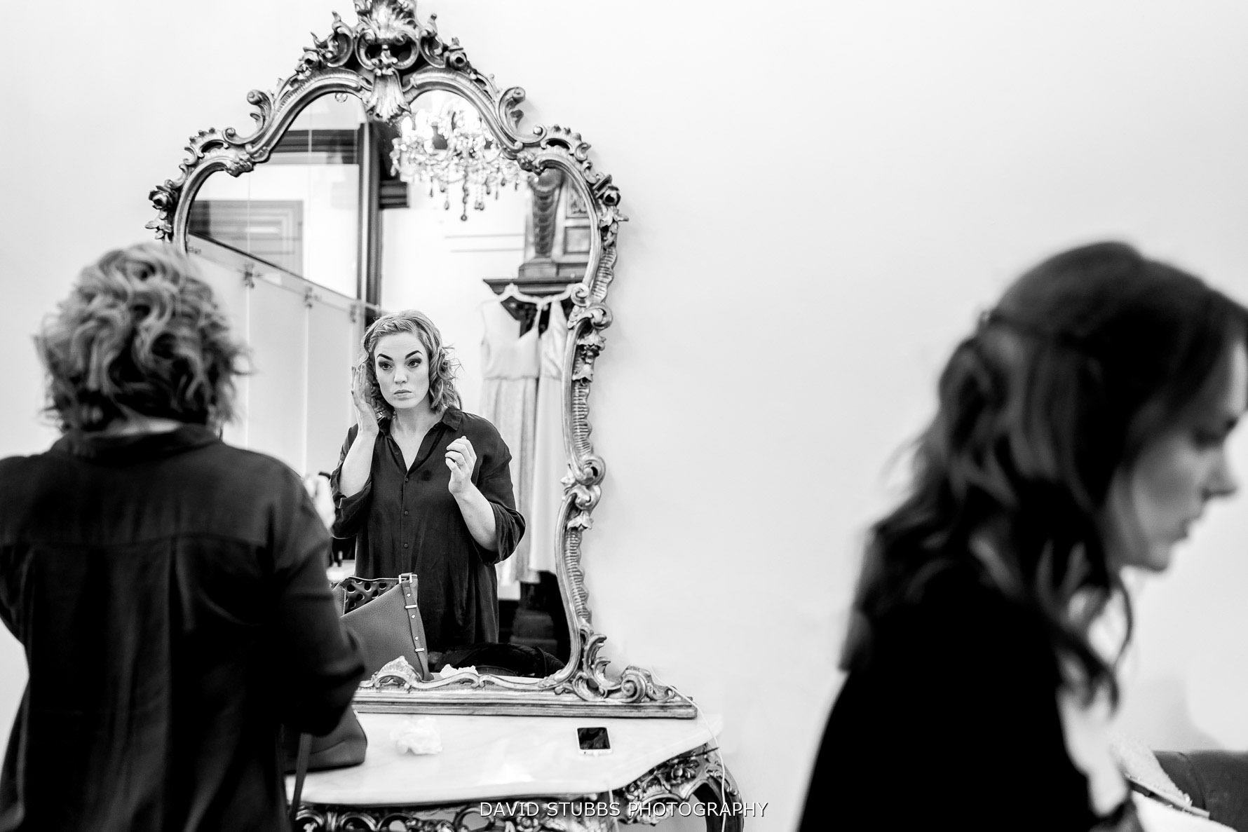 bride having make up done in mirror with reflection