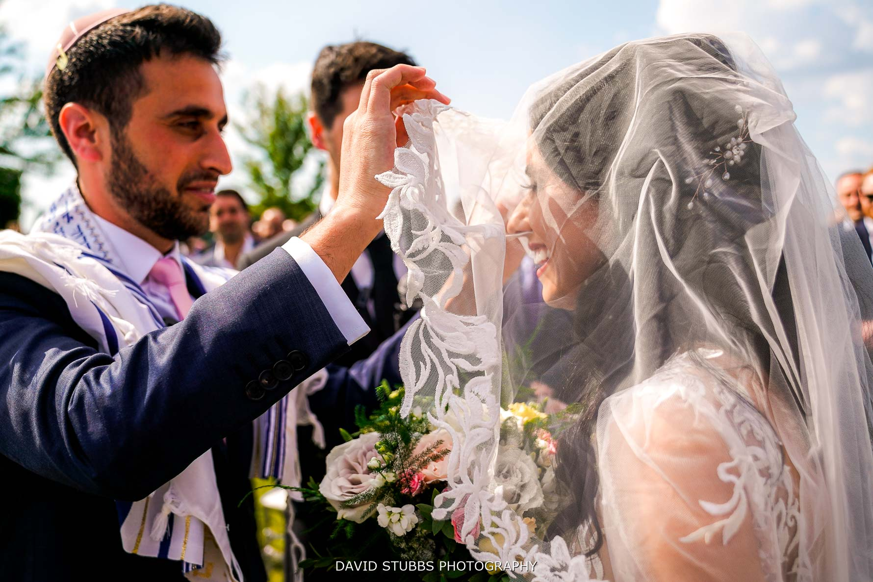 veil being lifted up by the groom