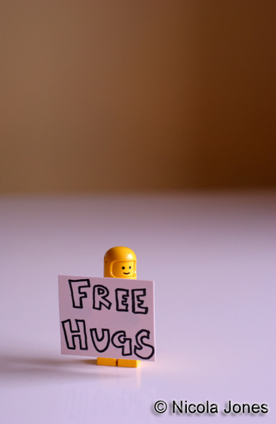Lego minifigure with Free Hugs sign.