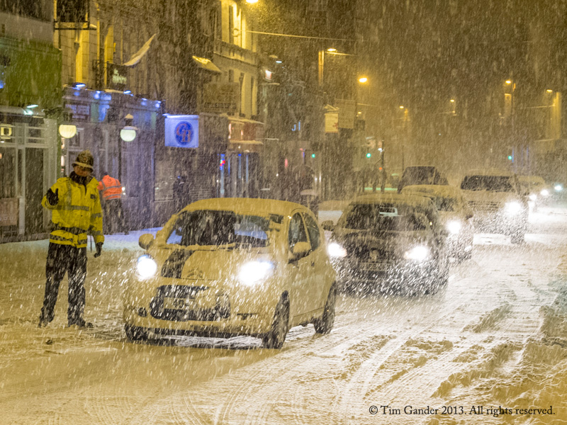 Police officer directs traffic in blizzard conditions in Bolton.