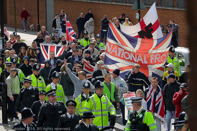 Supporters of the National Front are escorted through the streets of Bermondsey by police officers.