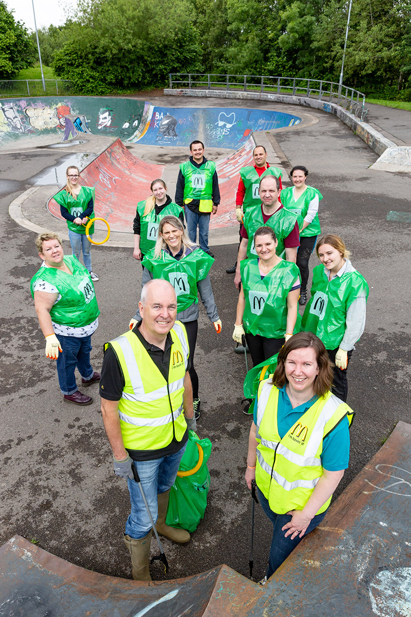 A team of litter pickers standing in a skate park in Peg Hill play area, Bristol.