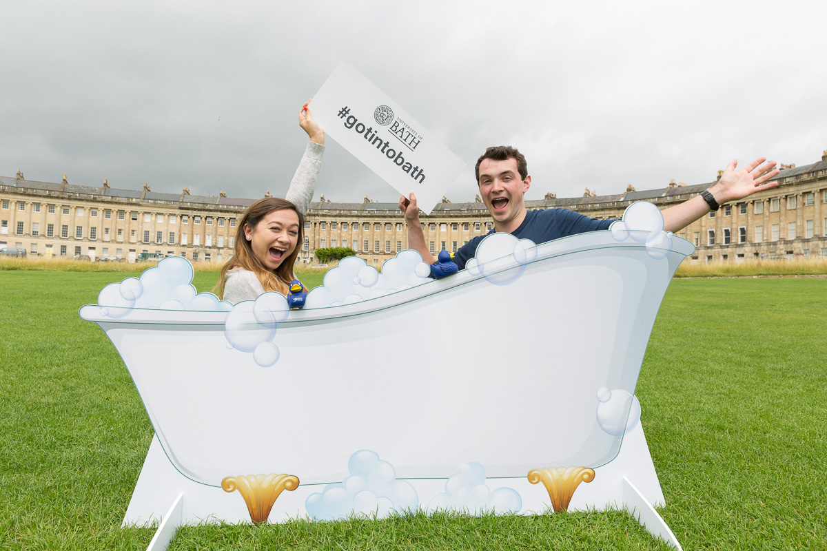 Got Into Bath social media campaign photo shows students Josh Bee and Tanya Savage posing with a cutout of a bath tub in front of Bath's Royal Crescent, holding a #gotintobath sign and waving, smiling to camera.