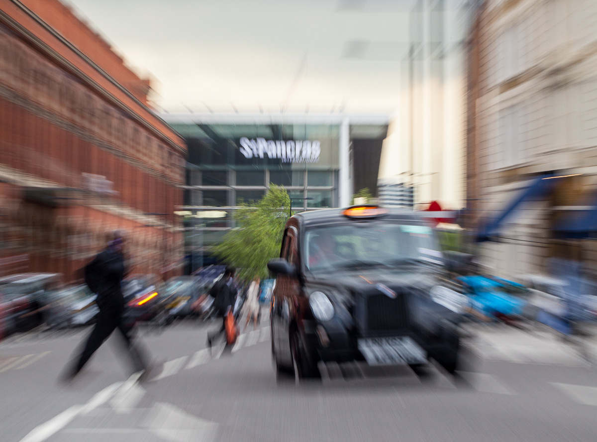 """A """"zoomed"""" view of St Pancras station, London with pedestrians and a taxi."""