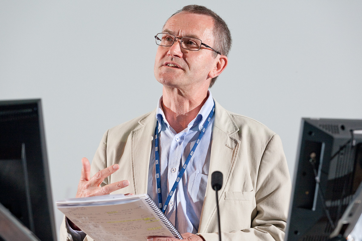 A male speaker in light fawn jacket and blue shirt speaks from notes at a University of Bath seminar.