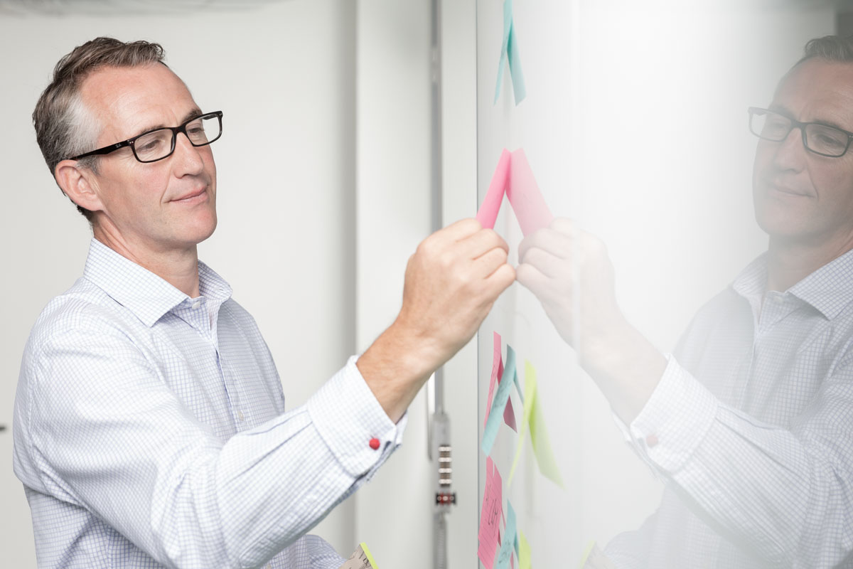 A business man places sticky notes on a gloss wall which reflects him.