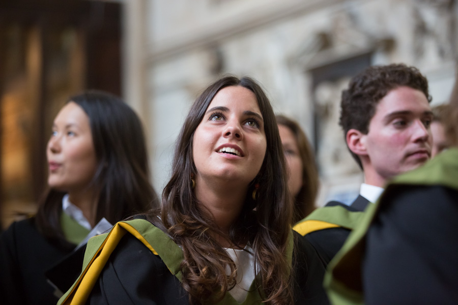 Original photo used for the University of Bath Impact Report cover shows a female graduate student looking upwards while waiting to collect her degree in Bath Abbey.