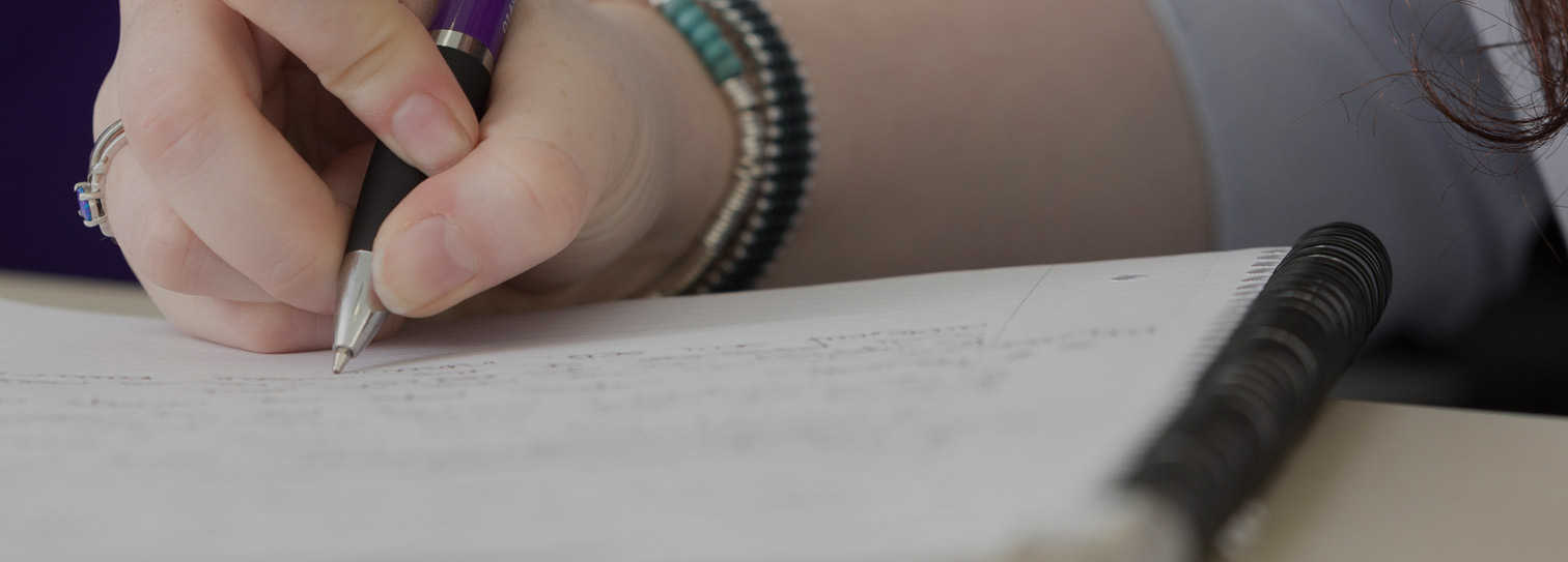 The hand of a Briscoe French colleague takes notes with a branded pen to illustrate their copywriting service.