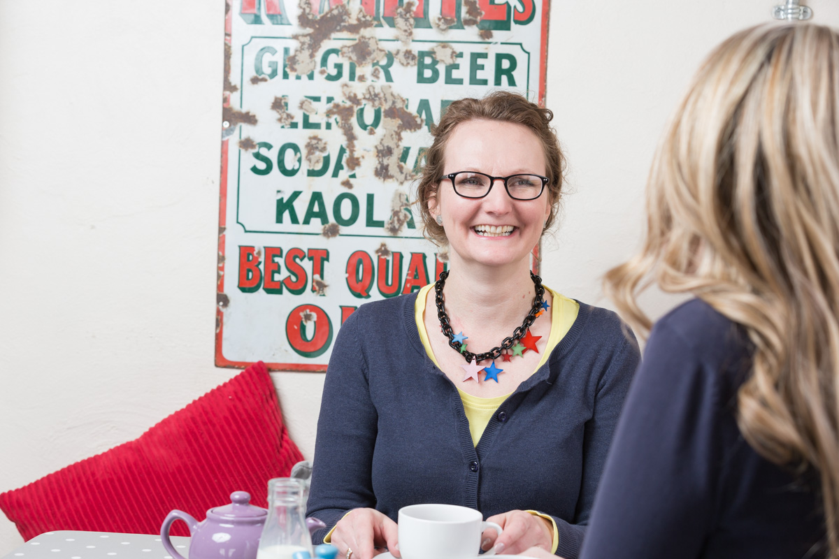 Michelle Gordon-Coles of Tea for Three sits chatting to a friend in a cafe over cups of tea.