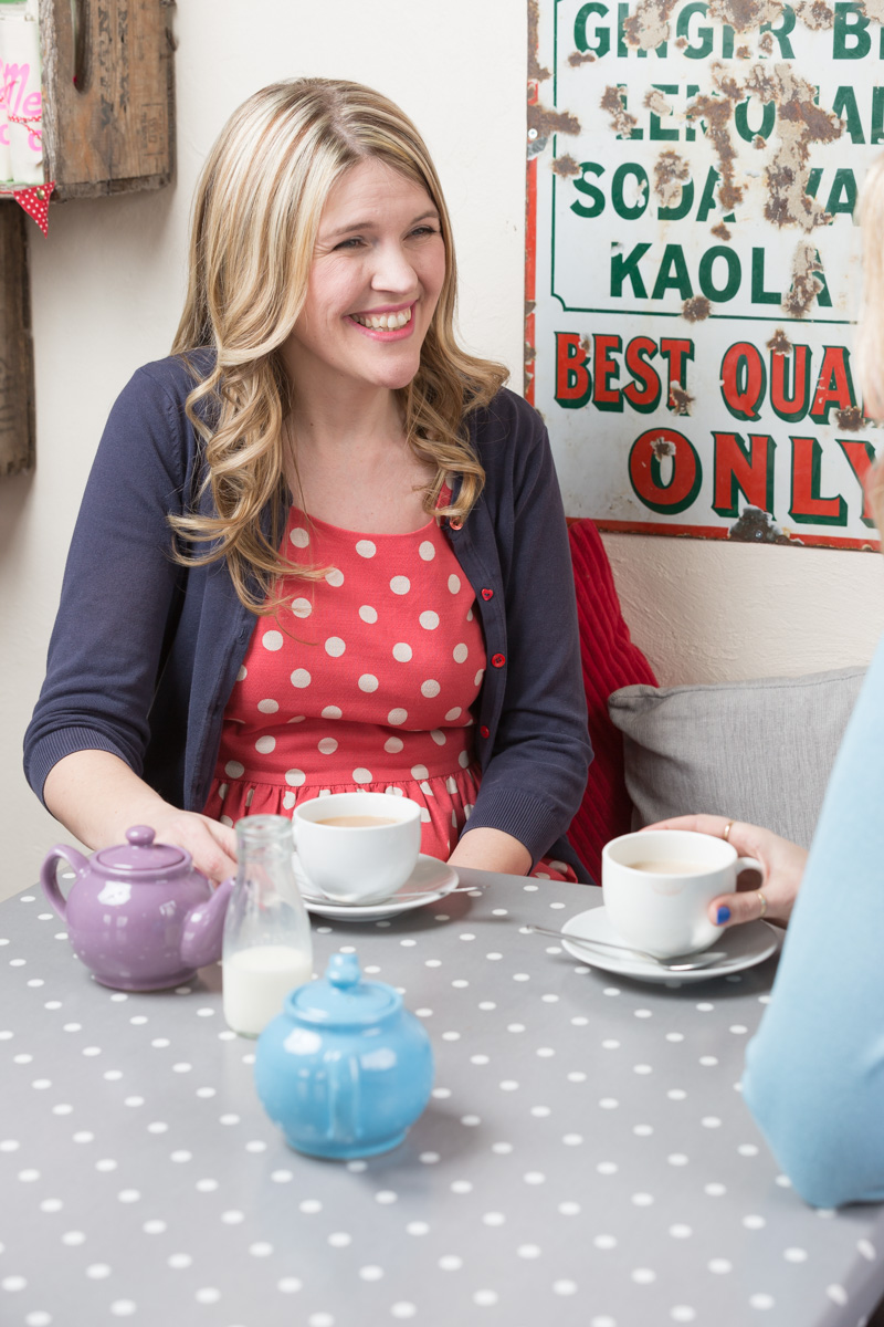 Helen Rimmer of Tea for Three sits chatting to a friend in a cafe over cups of tea.