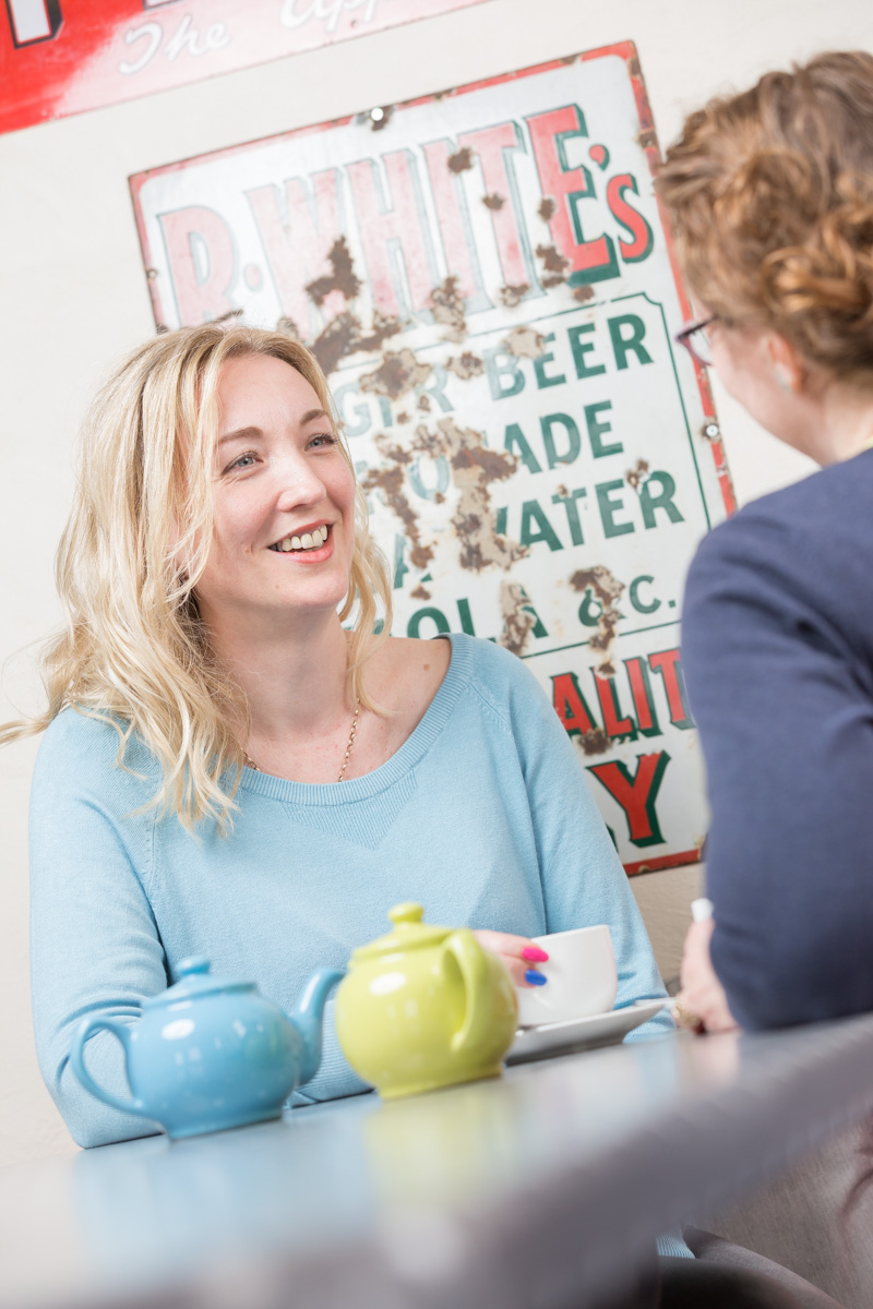 Debbie Clifford of Tea for Three sits chatting to a friend in a cafe over cups of tea.