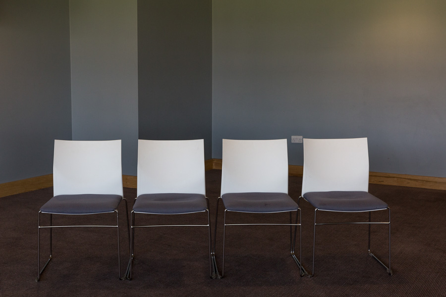 A row of 4 empty conference chairs against a grey wall with staggered corner and on brown carpet.