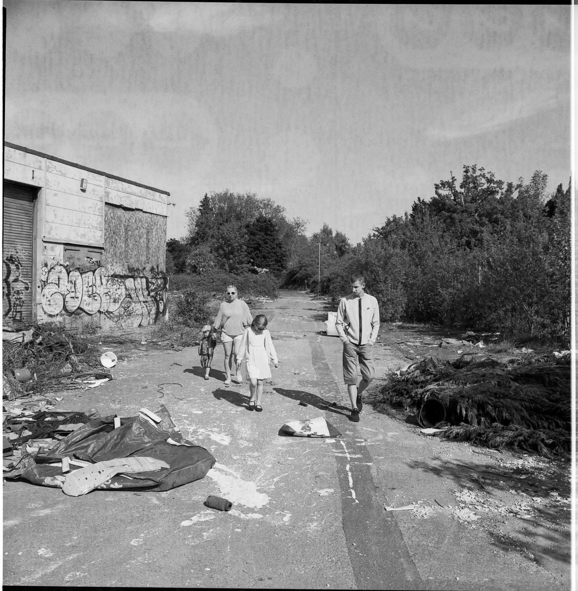 A family, mother, father, son and daughter walk through the derelict site.