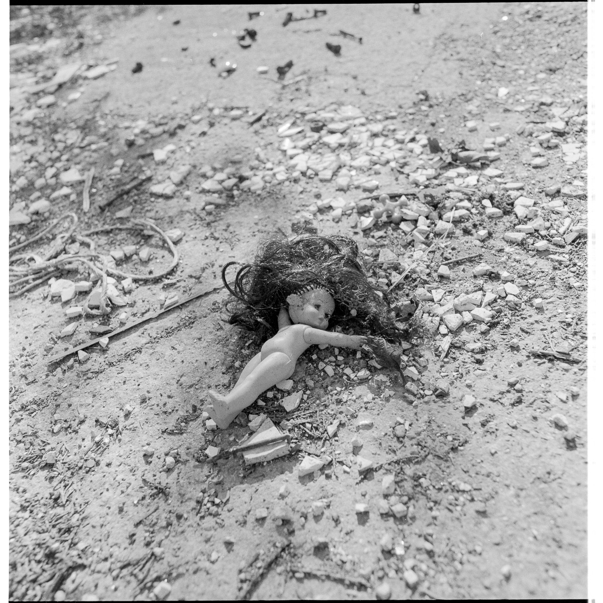 A small discarded plastic doll lies naked amongst scattered stones and other rubbish, her hair awry.