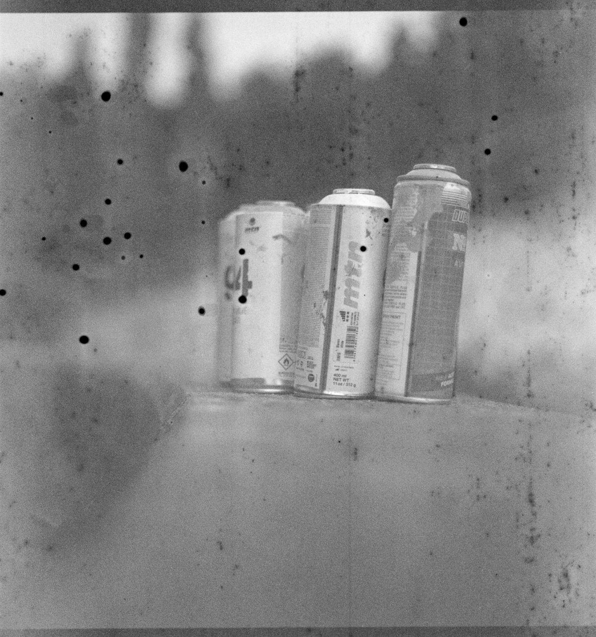 Discarded spray pint cans on a wall, highly degraded film results in black blobs and lines on the film.