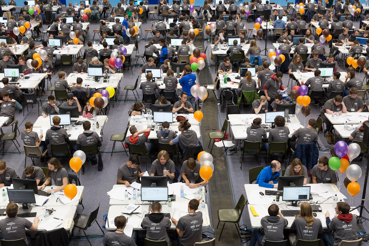 A high vantage point view of students at tables working at computers during the 2017 NWERC regional finals.