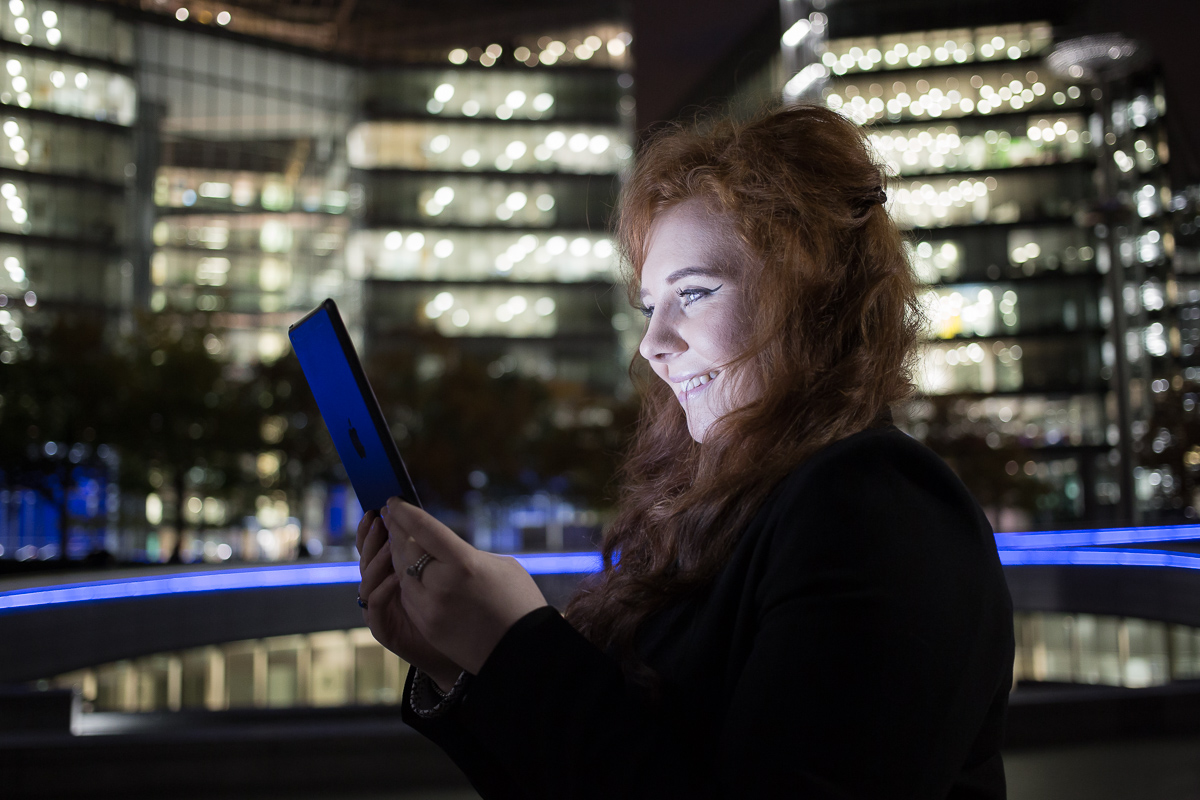 Side-portrait of a young business woman at night in London, her face illuminated by the iPad she is holding up to read. City office block lights illuminate the background.