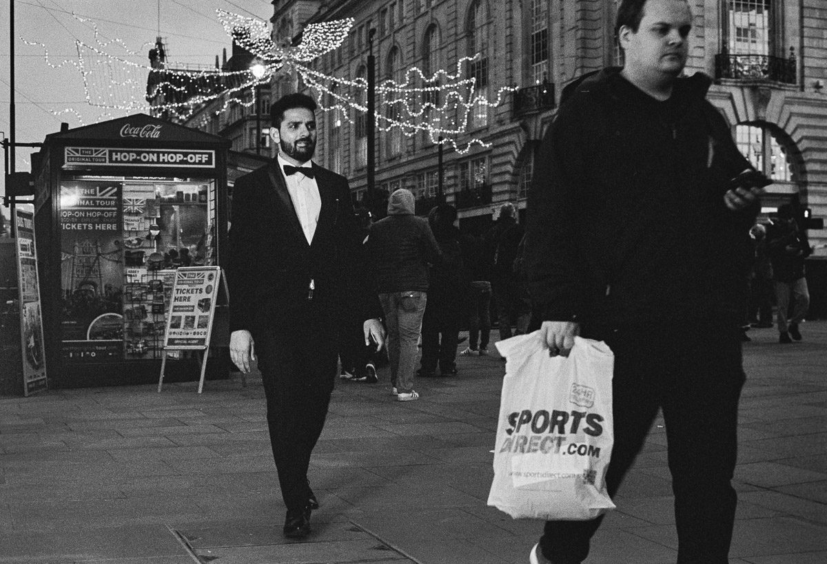 A man in the foreground walking to the right of the frame, carrying a Sports Direct plastic bag, is followed by a smart bearded man in a tuxedo and bow tie.