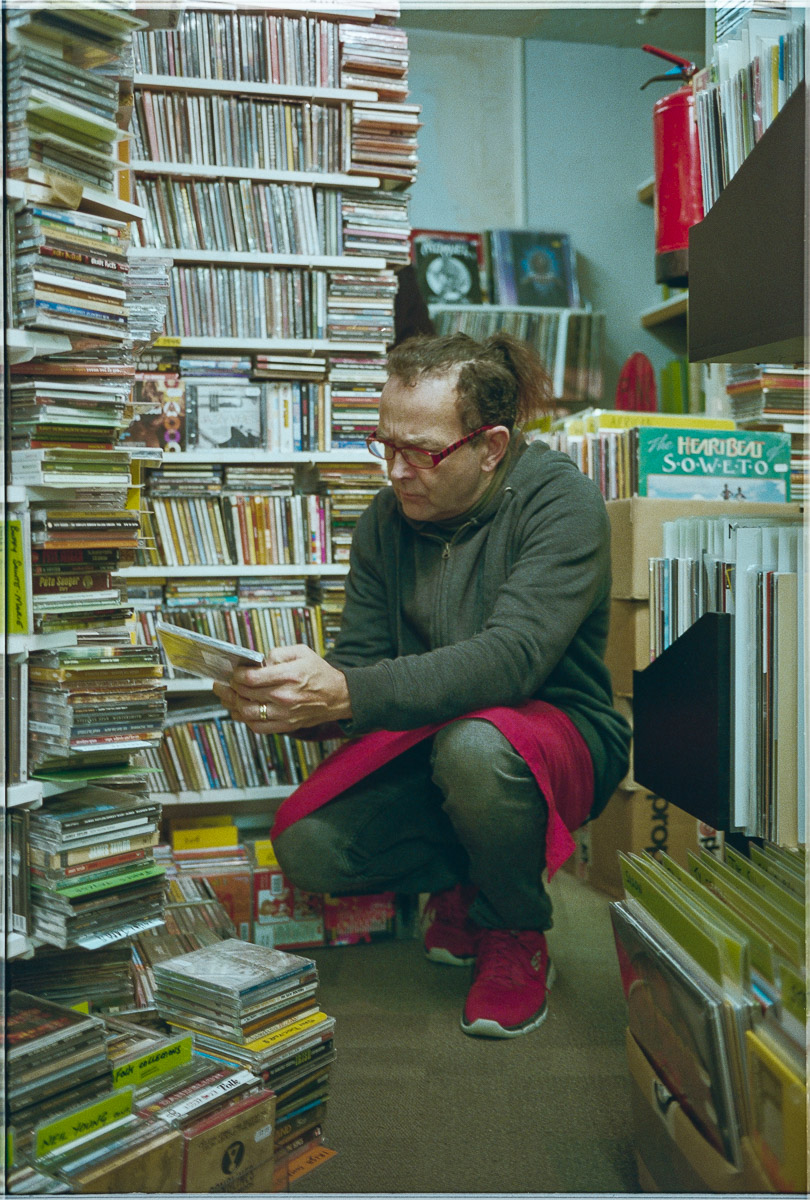 A shopper crouches to go through a selection of CDs.